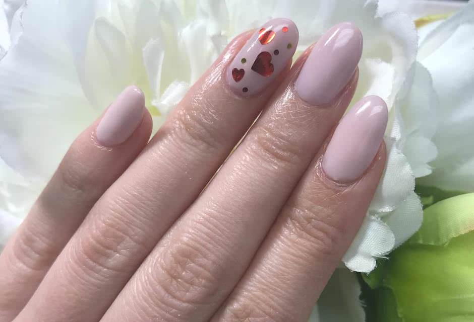 Unghie nude con nail art con cuori rossi San Valentino 2018