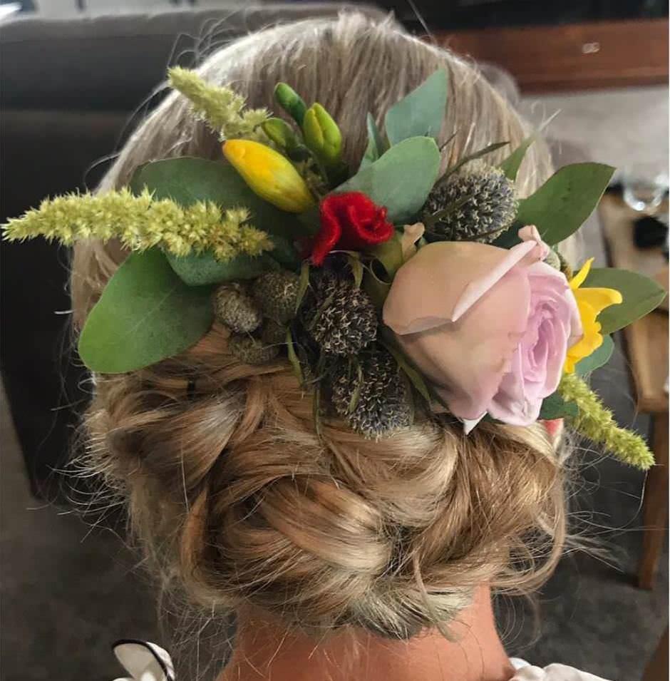 Acconciatura sposa 2018 con fiori colorati capelli raccolti