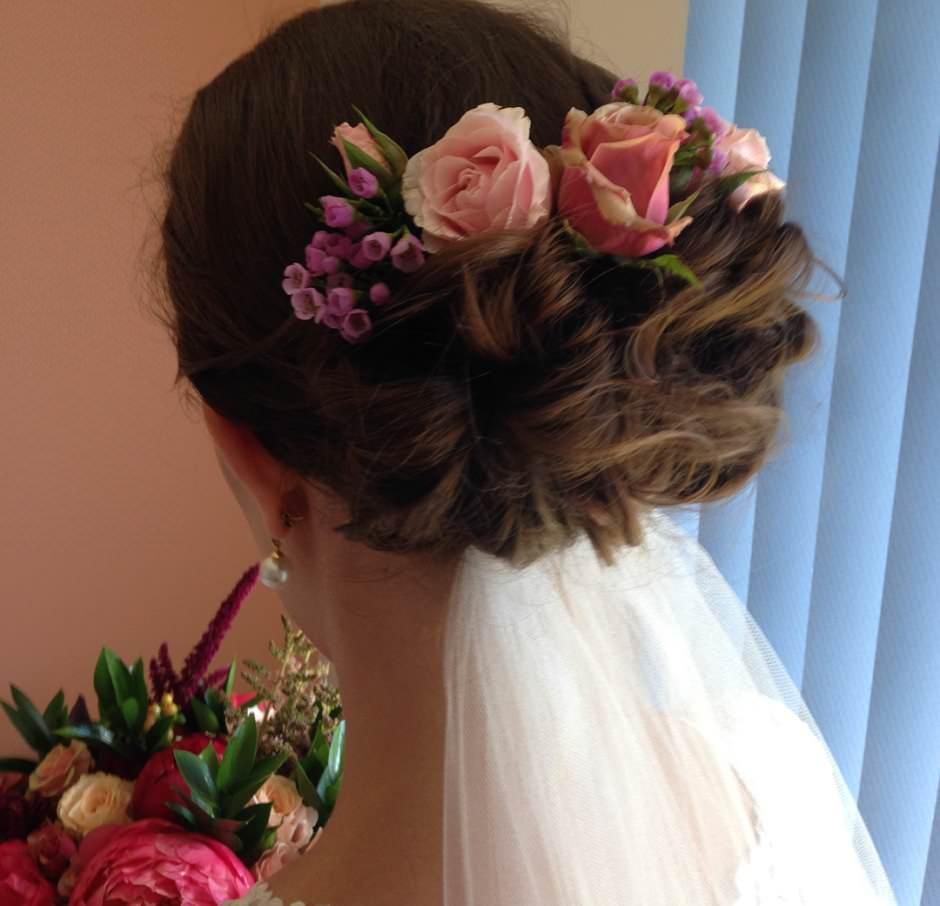 Capelli sposa raccolti con fiori e velo basso