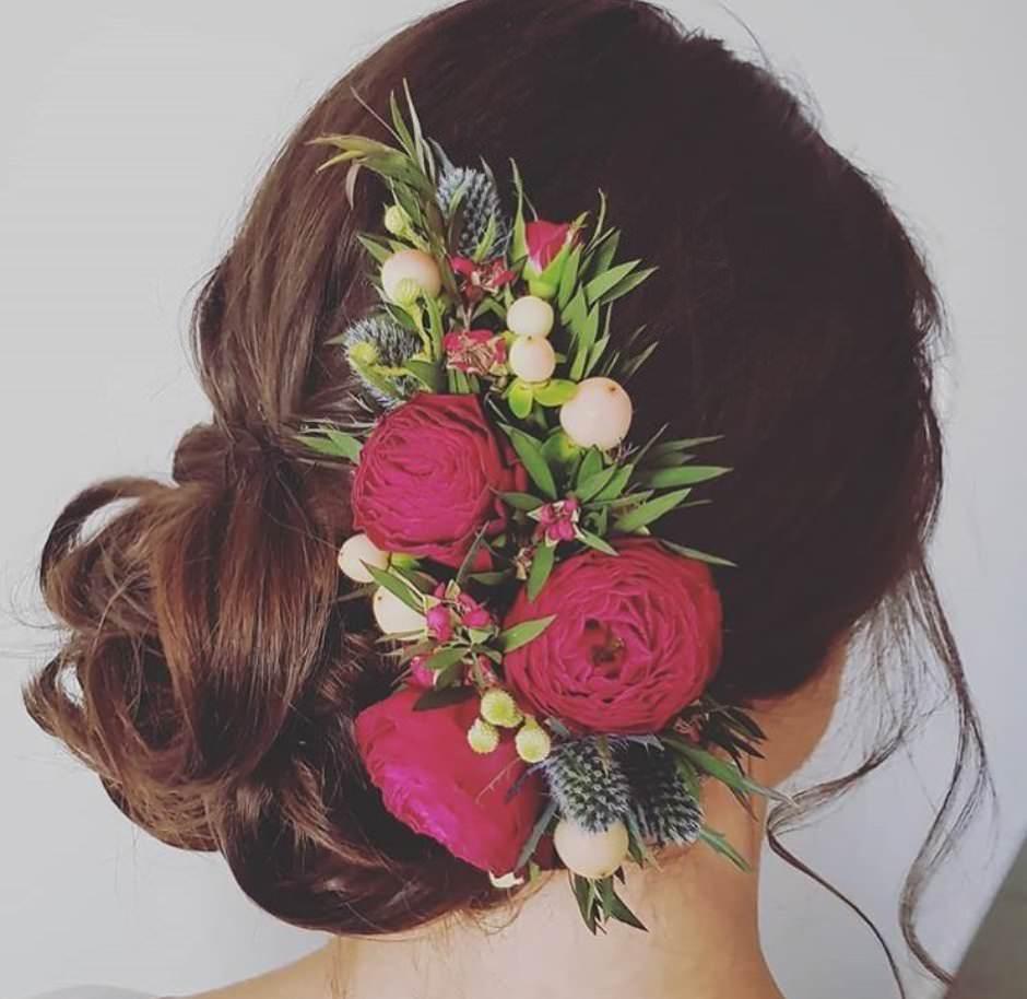 Acconciatura sposa con fiori rossi freschi